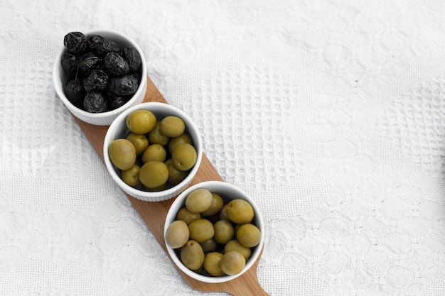 Set of three white bowls with olives on wooden tray on white blanket