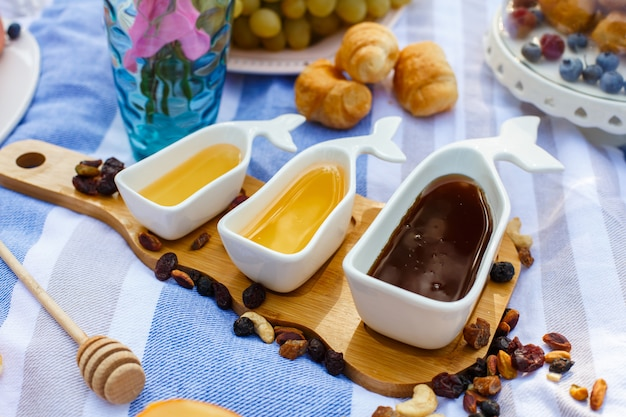 Set of three white sauceboats with sweet honey on wooden tray at picnic food lay out