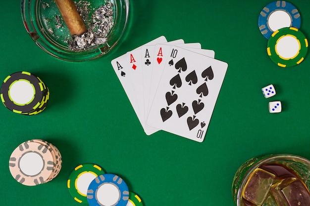 緑のテーブルでカードとチップを使ってポーカーをプレーするように設定します。コピースペースを使用して上から表示します。オンラインカジノのバナーテンプレートレイアウトモックアップ。緑のテーブル、職場の上面図。
