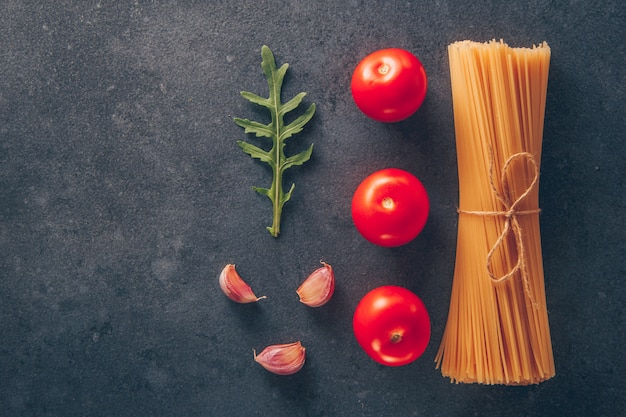 Set of tomatoes and garlic and spaghetti pasta on a gray textured background. top view. space for text