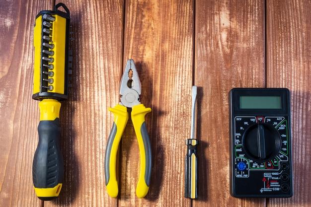 Set of tools for the electrician on a wooden table