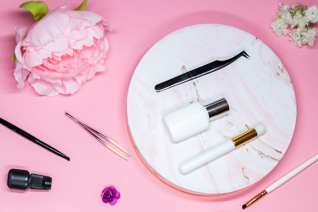 Set of tools for eyelash extensions on pink background