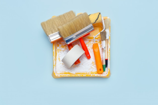 Set of tools for painting: paint brushes, masking tape, paint roller on light blue background.