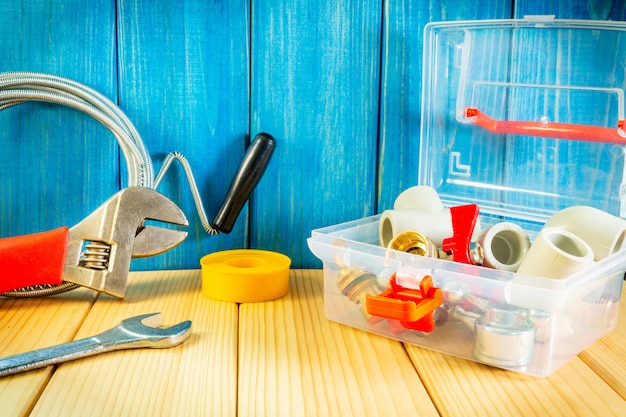 Set of tools and spare parts for plumbing folded on wooden boards after work or repair