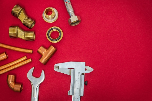 Set of tools and spare parts for plumbing on red background