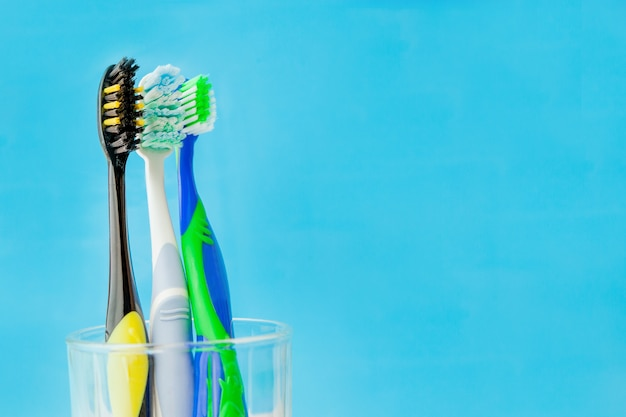 Set of toothbrushes in glass on blue wall. concept toothbrush selection, copy space