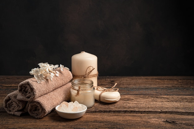A set of towels, candles, soap and salt on a dark background with space to copy.
