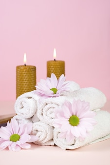Set of towels with flowers for spa treatments on a pink background. copy space