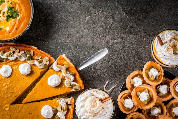 Set of traditional autumn food. halloween, thanksgiving. spicy pumpkin latte, pumpkin pie and tartalets with whipped cream and pumpkin seeds, pumpkin soup, on black stone table.  copyspace top view