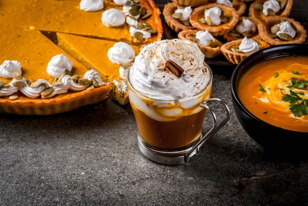 Set of traditional autumn food. halloween, thanksgiving. spicy pumpkin latte, pumpkin pie and tartalets with whipped cream and pumpkin seeds, pumpkin soup, on black stone table.  copyspace
