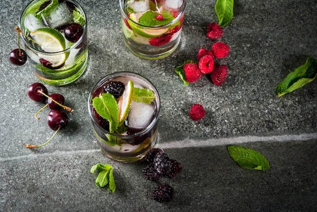 Set of traditional summer refreshing drinks berry mojito. with lime, mint leaves, blackberries, raspberries and cherries. with the ingredients on a dark stone table.