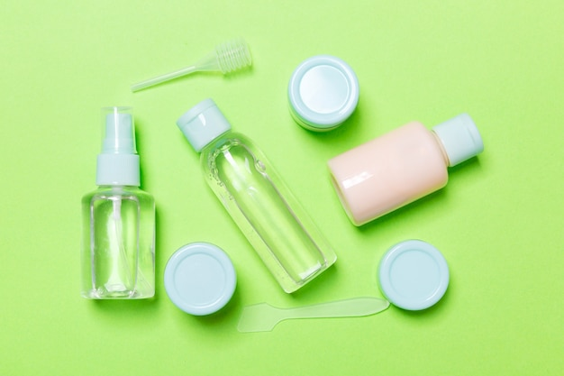 Set of travel size cosmetic bottles on green