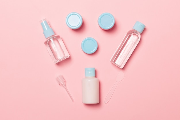 Set of travel size cosmetic bottles on pink