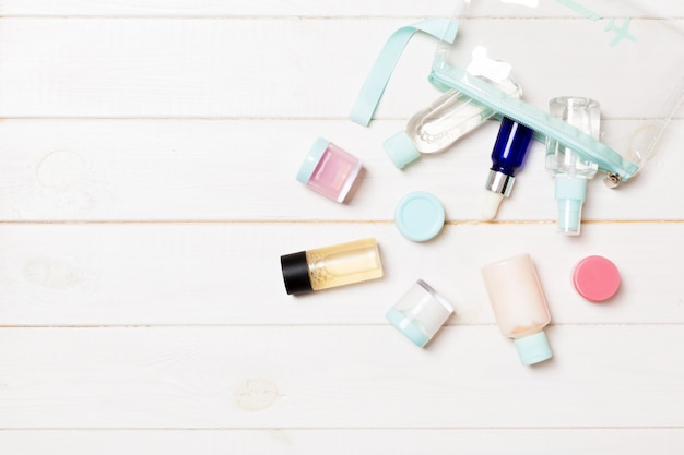 Set of travel size cosmetic bottles on white wooden background