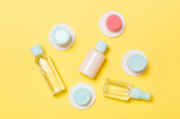 Set of travel size cosmetic bottles on yellow