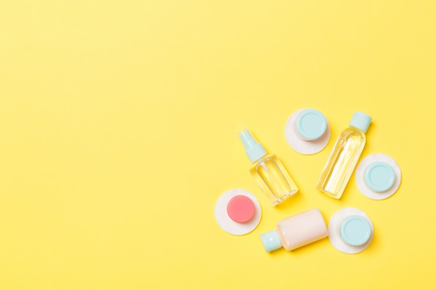 Set of travel size cosmetic bottles on yellow.