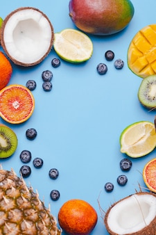 Set of tropical fruits kivi,blood orange, coconut, mango, blueberry, lime, kiv on blue backgroundi. ftropical fruits food frame. flatlay with copyspace. immunity consept