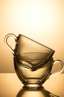 Set of two glass cups on a yellow