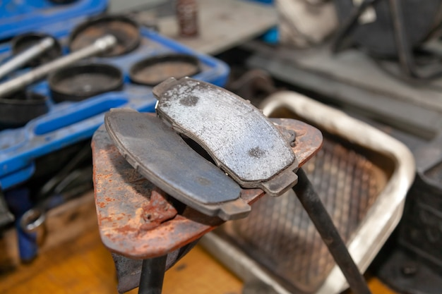 Set of two old automobile brake pads on a garage.