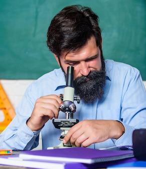 顕微鏡をセットアップします。先生は顕微鏡で机に座ります。生物学的観察で忙しい男のひげを生やした流行に敏感な教室の黒板の背景。顕微鏡を探している学校の先生。魅力的な研究。