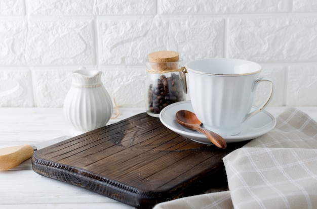 Set of utensils for coffee, a cup, a milkman and a can of coffee beans