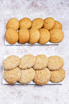 Set of various american style cookies on a light concrete background. shortbread with confetti, sesame seed, peanut butter, oatmeal and chocolate chip cookies.