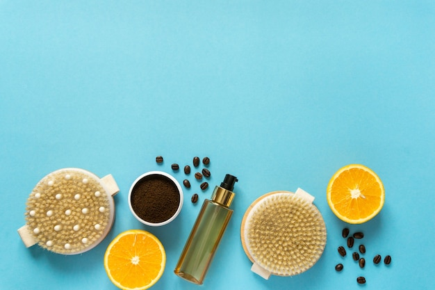 Set of various anti-cellulite care products. dry massage brushes, coffee scrub and oil on blue background, copyspace.