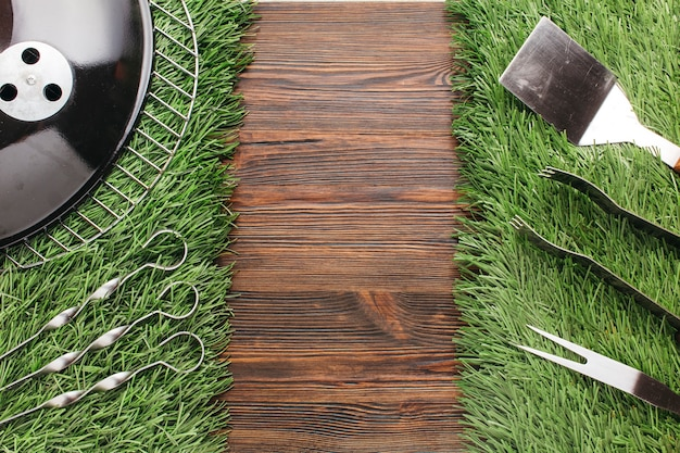 Set of various barbecue utensil on grass mat over wooden backdrop