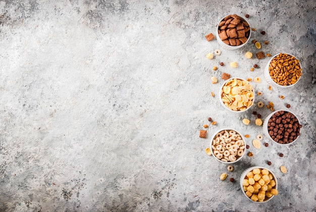 Set of various breakfast cereal corn flakes, puffs, pops, grey stone table copy space top view