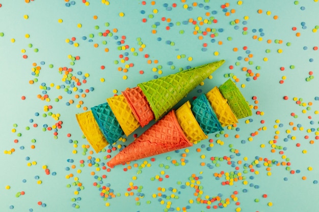 Set of various bright multicolored ice-cream waffle cones with scattered confetti sugar sprinkles.