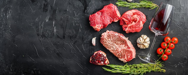 Set of various classic, alternative raw meat steaks with glasses of red wine over black background top view. big size space for text banner.