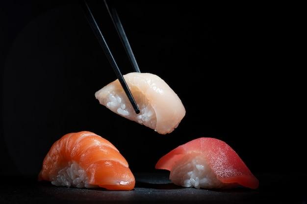 Set of various classic nigiri sushi on a black stone
