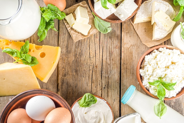 Set of various fresh dairy products - milk, cottage cheese, cheese, eggs, yogurt, sour cream, butter on wooden background