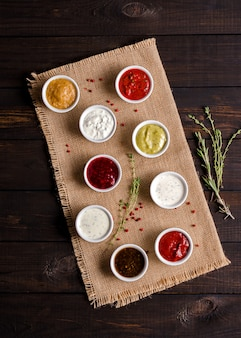 Set of various portioned sauces on a dark wooden rustic background. low key.
