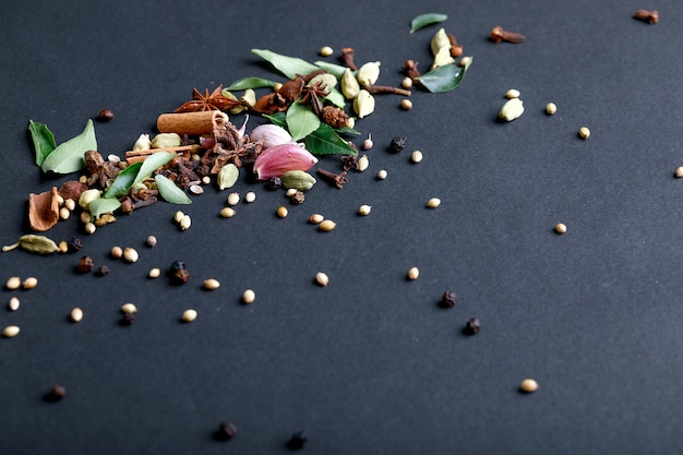 Set of various spices on black background.