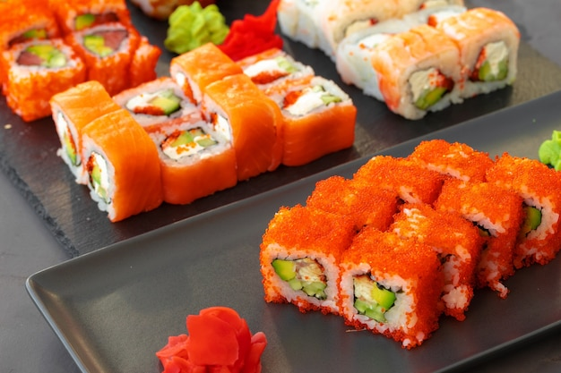 Set of various sushi rolls served on gray background close up