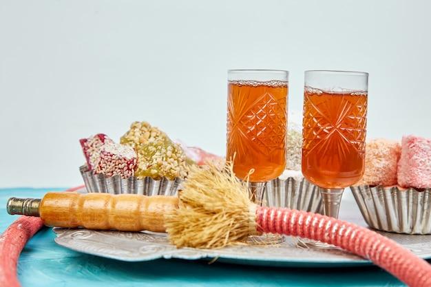 Set of various turkish delight in bowl on metal tray near hookah tube
