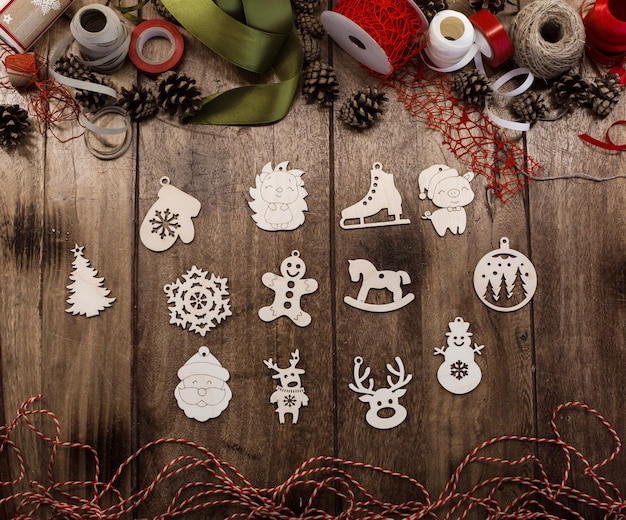 A set of various wooden christmas toys lie on a wooden table surrounded