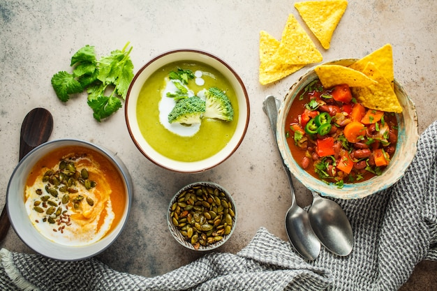 Set of vegan soups. mexican bean soup, broccoli cream soup and mashed pumpkin soup, top view.
