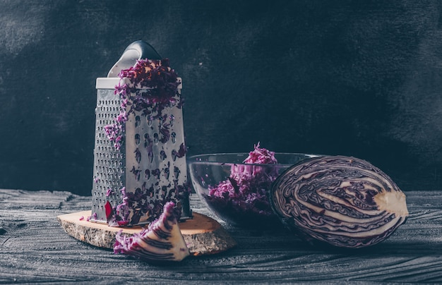 Set of vegetable grater and grated cabbage and red cabbage on a dark wooden background. side view.