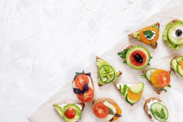 Set of vegetarian sandwiches on parchment paper on white textured background.