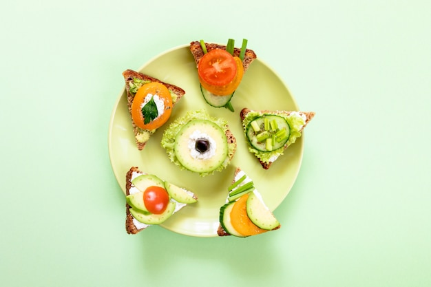 Set of vegetarian sandwiches on round green plate on green background.