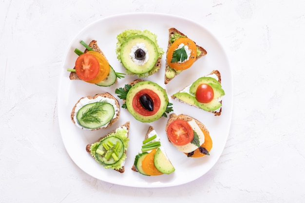 Set of vegetarian sandwiches on white plate on white textured background.