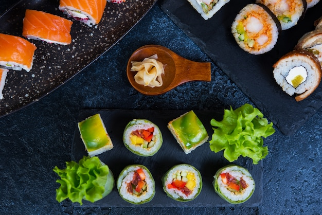 Set of vegetarian sushi rolls with lettuce leaves, vegetables and chinese chopsticks on a black background. traditional japanese food. top view.