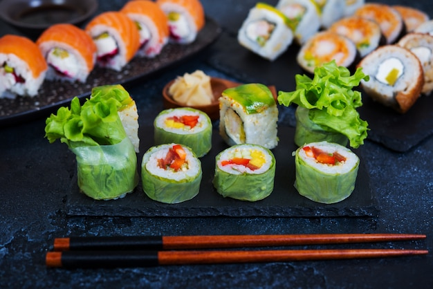 Set of vegetarian sushi rolls with lettuce leaves, vegetables and chinese chopsticks on a black background. traditional japanese food.