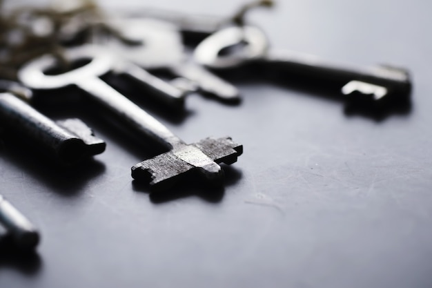 Set of vintage keys for a lock. retro keys on a dark stone background. the concept of choosing the path to achieve the goal.