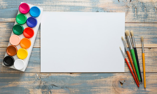 Set of water colors and paint brush with empty blank white paper over old wooden table