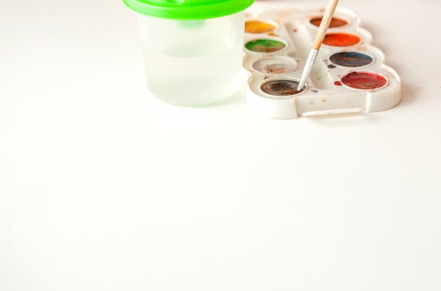 Set of watercolor paints and paintbrushes for painting on white background closeup, copy space. selective focus
