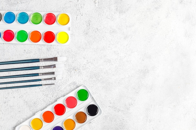 Set of watercolor paints and paintbrushes for painting.