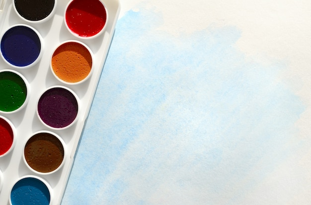Set of watercolors lies on a sheet of paper, which shows an abstract watercolor drawing